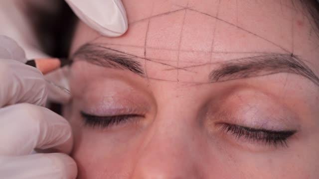 vidéos et rushes de le spécialiste dessine un croquis de sourcils. plan rapproché des formes géométriques claires sur le visage. 4k lente mo - sourcils