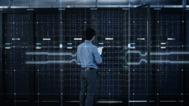 vídeos de stock e filmes b-roll de it specialist standing in front of server racks with laptop, he activates data center with a touch gesture. 3d animated concept of digitalization: network of lines spreading symmetrically. zoom out - technology