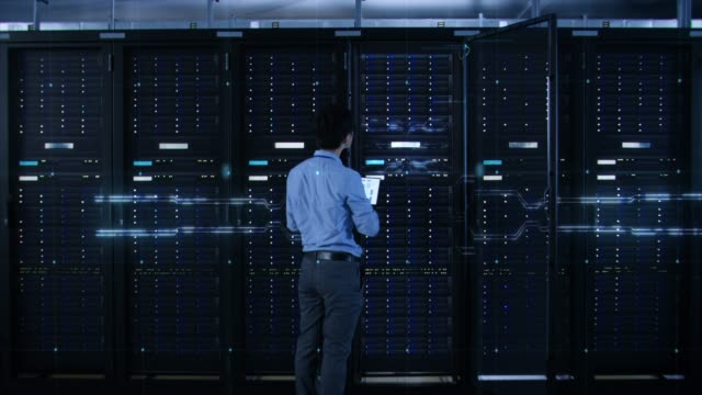 IT Specialist Standing In front of Server Racks with Laptop, He Activates Data Center with a Touch Gesture. 3D Animated Concept of Digitalization: Network of Lines Spreading Symmetrically. Zoom Out