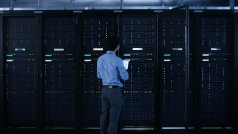 IT Specialist Standing In front of Server Racks with Laptop, He Activates Data Center with a Touch Gesture. Turning On New Data Center. IT Specialist Standing In front of Server Racks with Laptop, He Activates Data Center with a Touch Gesture. Turning On New Data Center. Shot on RED EPIC-W 8K Helium Cinema Camera. service stock videos & royalty-free footage