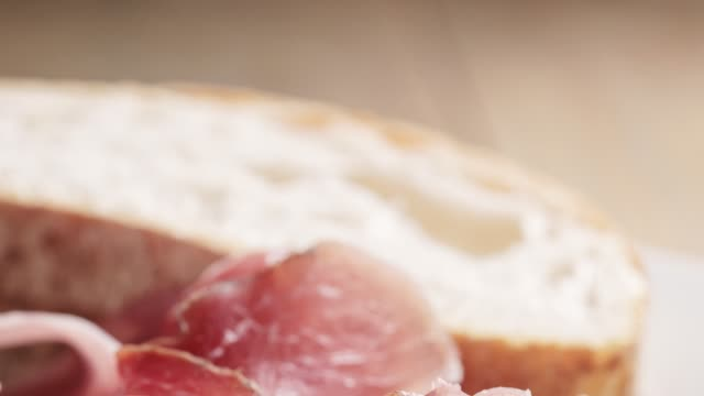 speck slices on white plate with ciabatta on old wood table video