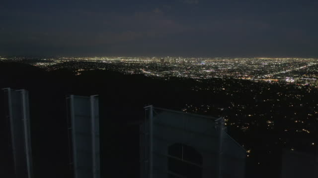aerial: spektakulära flight över letter o av hollywood sign på natten med los angeles city lights - hollywood sign bildbanksvideor och videomaterial från bakom kulisserna