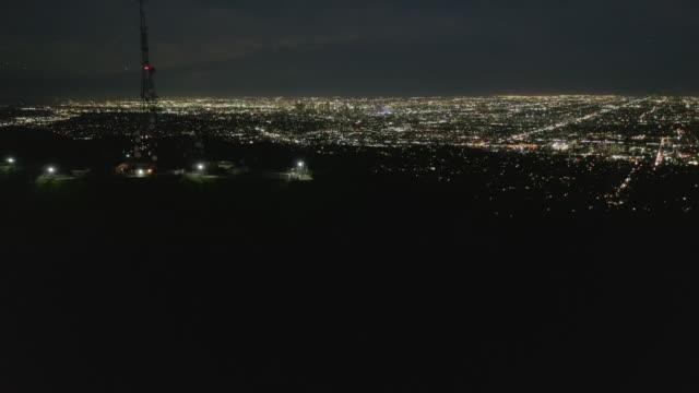 aerial: spektakulära flight över mount lee och hollywood sign at night med los angeles cityscape lights - hollywood sign bildbanksvideor och videomaterial från bakom kulisserna