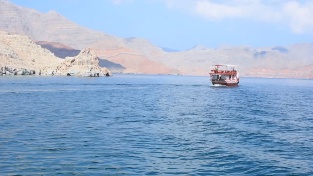 spectacular scenery panorama in musandam, oman on a vacation, tourist dhow boat trip through the fjords, rocky mountains, and blue water near strait of hormuz in the middle east. - oman filmów i materiałów b-roll