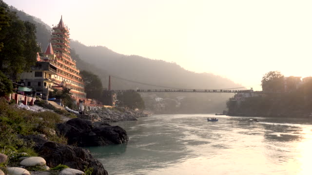spectacular view of the lakshman jhula bridge and the trayambakeshwar temple during the sunset. some people are doing rafting on the sacred river ganges. - tempio video stock e b–roll