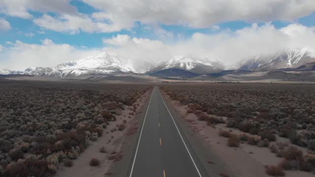 aerial: spectacular view of the majestic rockies and rugged wilderness in nevada - пешеходная дорожка путь сообщения стоковые видео и кадры b-roll