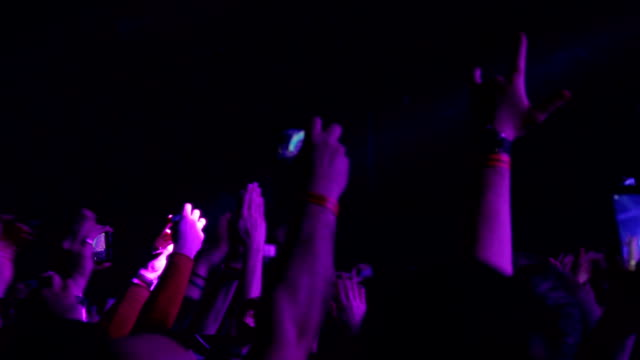 Spectators at a concert clap their hands and shoot on phones