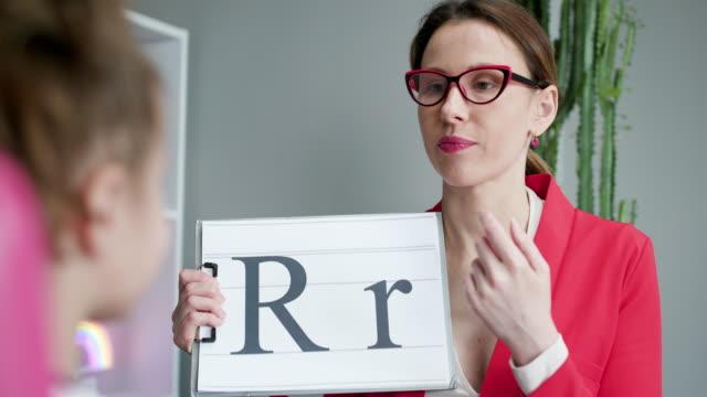 vidéos et rushes de orthophoniste retenant la lettre r et la fille arrière vue. orthophoniste enseigne aux filles à dire la lettre r - professeur(e)
