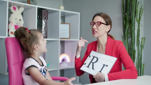 vidéos et rushes de l'orthophoniste enseigne aux filles à dire la lettre r. femme orthophonothérapeute enseignant la prononciation préscolaire kid sound. concept de leçon de discours de problème de capacité vocale - professeur(e)