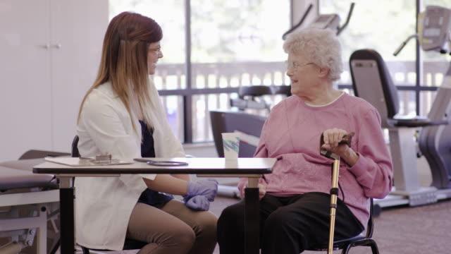 vídeos y material grabado en eventos de stock de terapeuta del habla trabajan con un paciente geriátrico en una clínica - geriatría