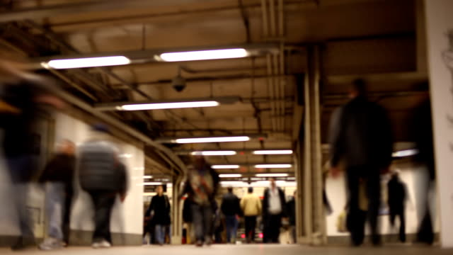 Speed and pace of daily subway commuters in NYC. Commuters walking through tunnel in Manhattan. defocused. 12x time lapse. new york city subway stock videos & royalty-free footage