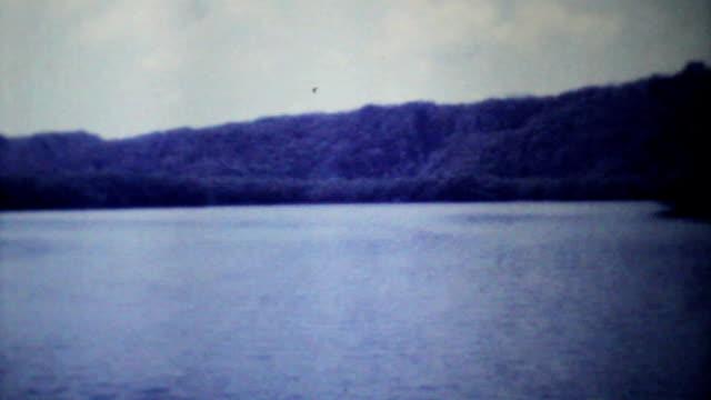 vídeos de stock e filmes b-roll de velocidade do barco cruising sobre o oceano - 1979 vintage 8 mm film - américa do sul