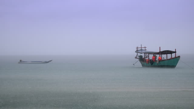 vídeos y material grabado en eventos de stock de lancha rápida atada junto a un barco de pesca de cola larga fuera de la costa en un día lluvioso - anclado