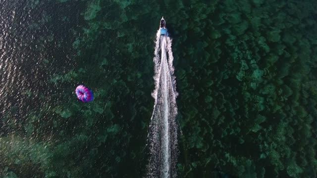 vídeos de stock, filmes e b-roll de lancha com antena de para-quedas - paraquedismo
