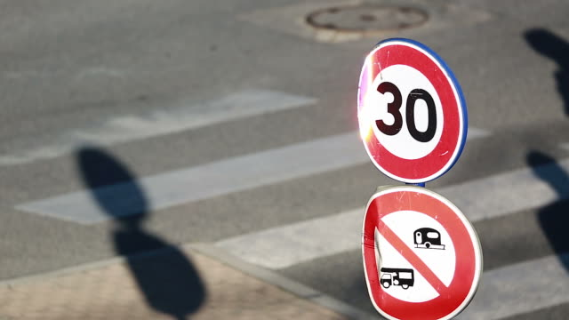 speed restriction road sign and pedestrian crossing the street - 30 34 anni video stock e b–roll