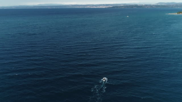 Speedboat moving along the coastline - aerial view video