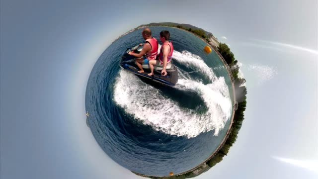 Speeding men on a jetboat filming with a monopod