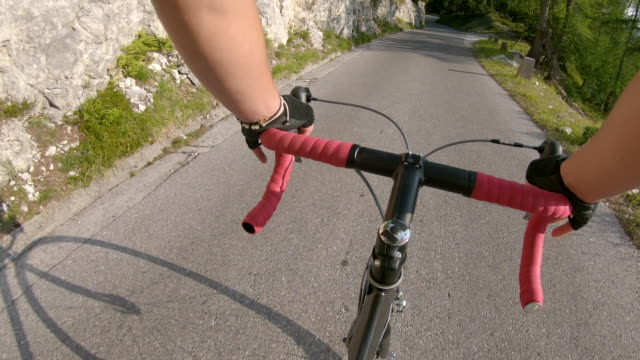 vidéos et rushes de pov: excès de vitesse à vélo vers le bas d'une route d'asphalte vide qui traverse la forêt - moto sport