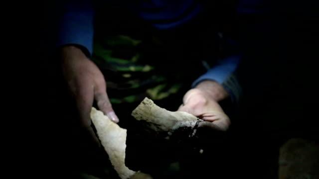 speleology explorer in a cave examining ancient rocks video