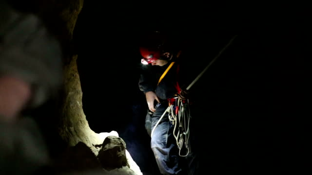 speleology explorer in a cave examining and securing a bolt on a rock 1 speleology male working in a deep and dark pit . preparing to drill and secure this pit with bolts cave stock videos & royalty-free footage