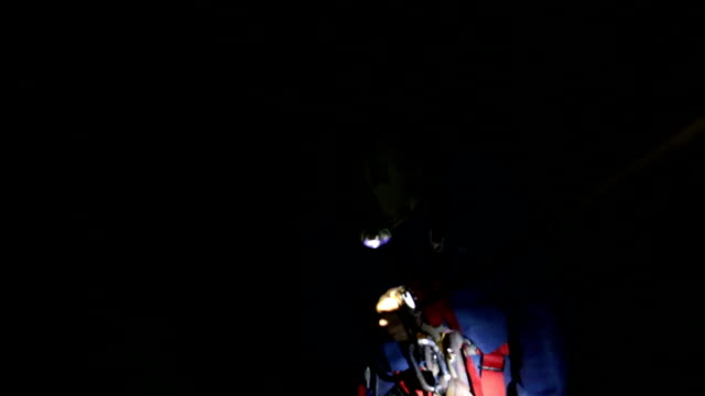 speleology explorer in a cave examining climbing up on a rope from a deep pit video