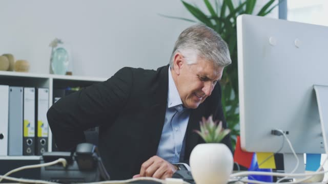 Spending too much time behind his desk 4k video footage of a mature businessman suffering with back pain while working in his office pain stock videos & royalty-free footage