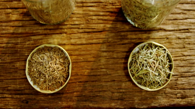 Spices in jar and lid on wooden table 4k video