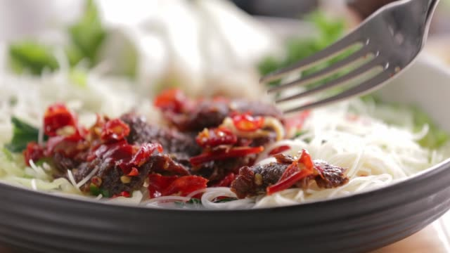 spicy beef with rice noodles taken by fork - chilli con carne video stock e b–roll