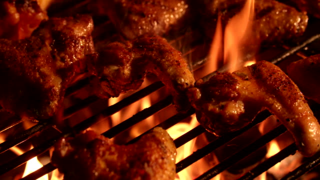 Spicy chicken wings grilling over glowing coals of a barbecue video