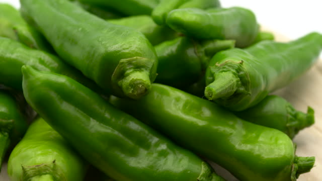 spicy green chili peppers rotating on wooden background. healthy eating concept - paprica video stock e b–roll