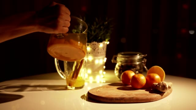 Spicy tea in a cup with cinnamon, honey, turmeric on a wooden background. Hot drink. Copy space. Christmas lights Spicy tea in a cup with cinnamon, honey, turmeric on a wooden background. Hot drink. Copy space. Christmas lights ginger spice stock videos & royalty-free footage