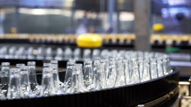 Spill in glass bottles at the plant. Conveyor belt with beer bottles video