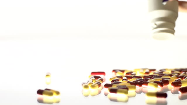 HD SLOW MOTION: Spilling Capsules HD1080p: SLOW MOTION shot of a woman's hand spilling capsules out of a pill bottle over a glass surface. pill bottle stock videos & royalty-free footage