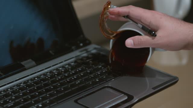 spilling coffee on laptop computer slow motion - сломанный стоковые видео и кадры b-roll