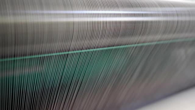 vidéos et rushes de broche avec du fil blanc dans l'usine de jean - fibre