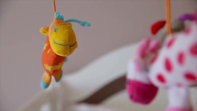 spinning baby toys above the baby's bed - giocattolo video stock e b–roll