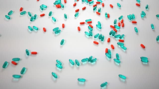 Spinning blue and orange pills over white studio background - Above Angle view video