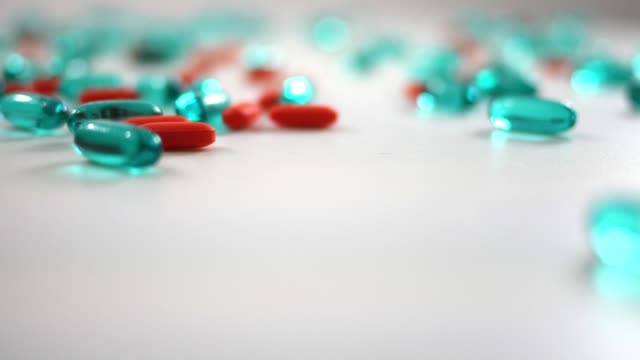 Spinning blue and orange pills over white studio background - bokeh depth of field video