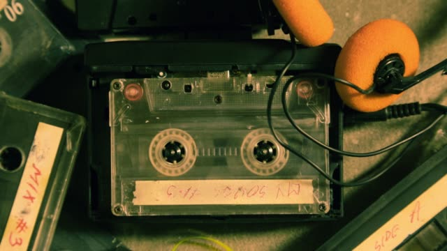 spinning cassette tape in a walkman and a few old cassettes - cassetta video stock e b–roll