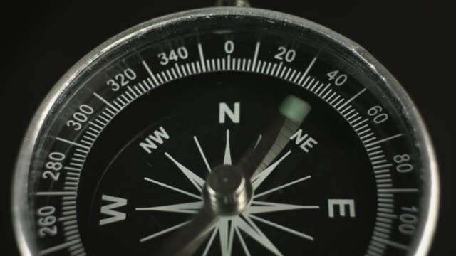 Spinning compass arrow points to North Isolated compass with revolving arrow pointing to North, close-up navigational compass stock videos & royalty-free footage