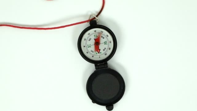 Spinning Compass Needle A simple stationary fast spinning black open compass with a white background and red string necklace viewed from above. Zoom in. magnet stock videos & royalty-free footage