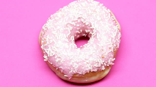 Spinning donut on pink table, high-sugar dessert causes diabetes, temptation