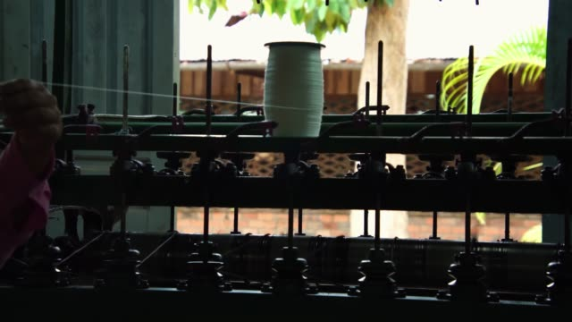Spinning silk fibers into threads, before silk is woven into textiles. Raw silk handmade production in village factory.
