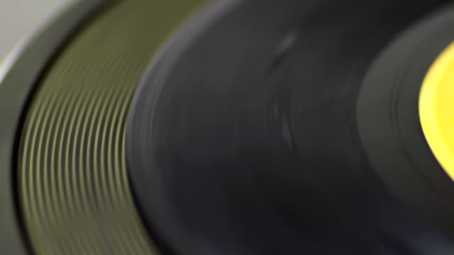 Spinning Vinyl Macro shot of old vinyl recording rotating in vintage player. Good for record player, gramophone, party, DJ, music, and more. Turntable On-Off. grooved stock videos & royalty-free footage