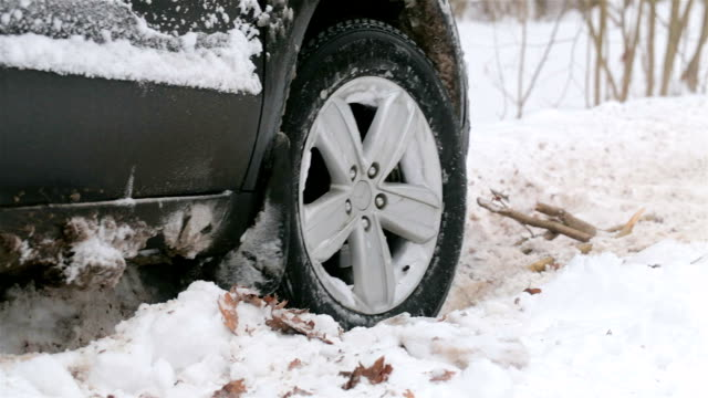spinning wheel of a car stuck in snow. - scivolo video stock e b–roll