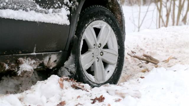 snurrande hjul på en bil fastnat i snön. - fånga bildbanksvideor och videomaterial från bakom kulisserna