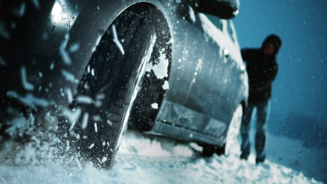 SLO MO Spinning wheel of a car stuck in snow