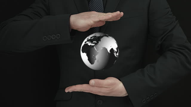 Spinning World Globe Appearing Between Businessman Hands video