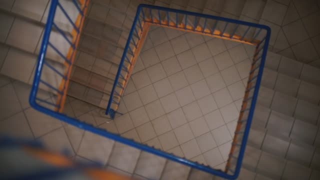 bir kare şeklinde yapılmış bir apartmanın spiral merdiven. - avize aydınlatma ürünleri stok videoları ve detay görüntü çekimi