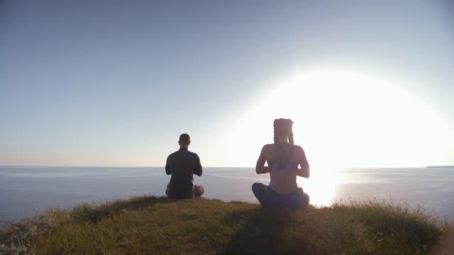 ruhani dünya, adam ve kadın dağ üstünde oturan denizde lotus pozisyonda meditasyon deniz bakıyor, arka görünüm - i̇nsan sırtı stok videoları ve detay görüntü çekimi